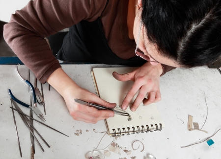 Bird eye view of a female jeweler working in her workshop.