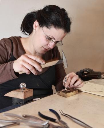 trabajo manual: Imagen de primer plano de un joyero femenino clavar un trozo de metal en su taller. Hay un desenfoque de movimiento previsto en el martillo.