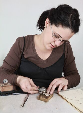 jeweller: Close-up image of a female jeweler working on a piece of metal in her workshop. Stock Photo