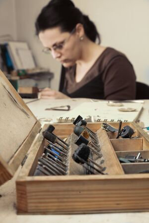craftsmanship: Selective focus on the opened wooden toolbox , in front of a femeale jeweler working in her workshop.