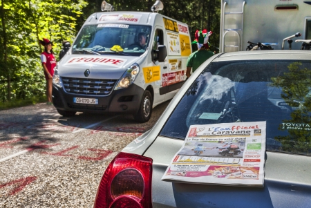 gazette: Col du Granier,France-July 13th, 2012: The official daily newspaper (LEaufficiel de la Caravane) is on a car parked on the side of the road to mountain pass Granier during the passing of the Publicity Caravan in the 12th stage of Le Tour de France 2012.  Editorial