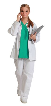 unifrom: Image of a young female doctor on the phone holding a clipboard and walking to the camera, isolated against a white background.