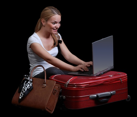 Young blonde woman checking her computer in a hurry on her red suitcase,isolated against a black background. photo