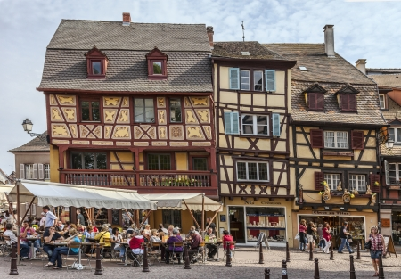 french cafe: Colmar,France- April 23rd, 2011: People relaxing on street terraces in a town square near traditional half-timbered houses in Colmar, Alsace, France.