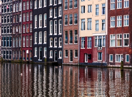 urbanscape: Typical colorful facades of houses and their reflections in a water canal in Amsterdam.