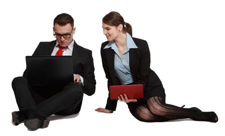 Young business couple sharing one another's work on their laptops while sitting against a white background. photo