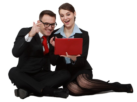 Happy young business couple looking at the notebook while sitting against a white background  photo