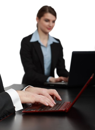 Close-up image of masculine hands working on a red notebook in front of a young woman using a laptop on a black table in an office  photo