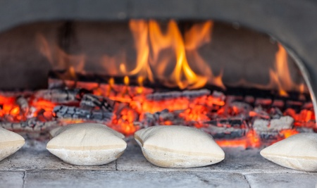 woodfired: Image of traditional French small breads in front of an ancient firewood oven. Stock Photo