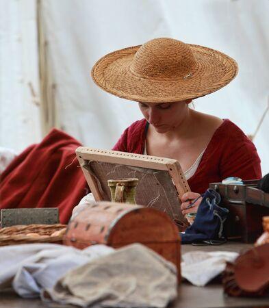 trabajo manual: Nogent le Rotrou, Francia, 12.5.2013: Retrato ambiental de una dama medieval joven que teje bajo su carpa durante el Festival Medieval Percheval, cerca de Saint Jean Castillo en Nogent-le-Rotrou. Editorial