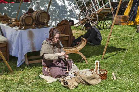 deftness: Nogent le Rotrou,France, 11.05.2013: Medieval young woman spinning wool outside of the tent during the Percheval Medieval Festival, near Saint Jean Castle in Nogent le Rotrou.