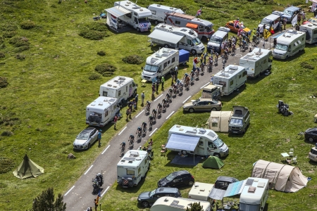 Col de Pailheres,France- July 07 2013: The peloton climbing the road to Col de Pailheres in Pyrenees Mountains, through a row of caravans and spectators during the stage 8 of the 100 edition of Le Tour de France on 7 July 2013.