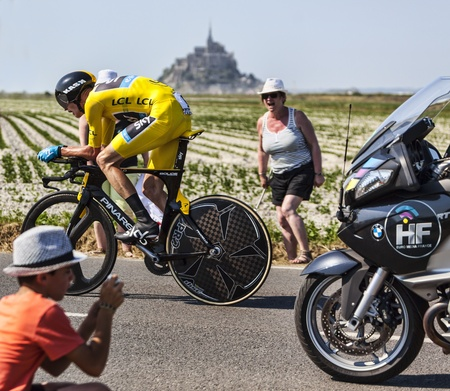 Le Poont Landais,France-July 10, 2013: The Yellow Jersey ( Chris Froome, Great Britain) pass through a group of excited spectators in front of the Mont Saint Michel monastery, during the stage 11 of the edition 100 of Le Tour de France 2013, a time trial  Stock Photo - 20804235