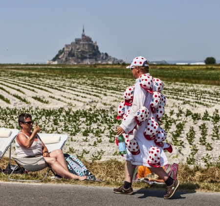 carrefour: Le Pont Landais,France-July 10, 2013: Unidentified man funny disguised walking in the vicinity of Le Mont Saint Michel monastery during the stage 11 of the edition 100 of Le Tour de France 2013, a time trial between Avranches and Mont Saint Michel. Editorial