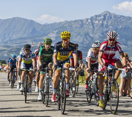 Col de Manse, France- July 16, 2013: The peloton pedaling on a plain road after the ascension to Col de Manse in The Alps during the stage 16 of 100th edition of Le Tour de France 2013.