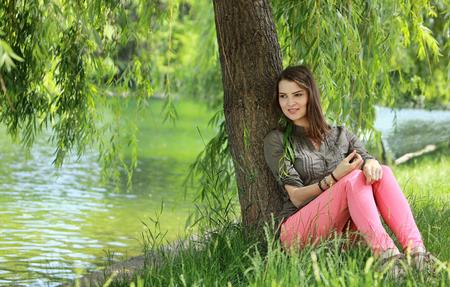 sauce: Joven mujer de relax bajo un sauce cerca de un estanque en un parque en verano.