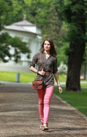 Beautiful young woman walking in a park in summer photo