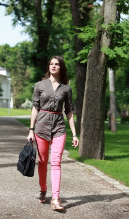 Beautiful young woman with a latop bag walking in a park in summer photo