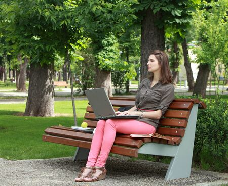 sitting on a bench: Young woman sitting on a bench in a park and working on a laptop.