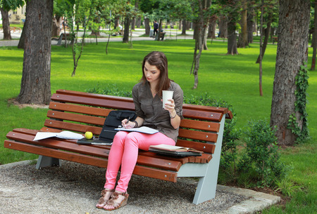 sitting on a bench: Young woman sitting on a bench in a park and writing something in a notebook while holding a disposable cup of coffee.
