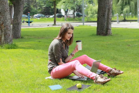 Young student woman holding a disposable cup of coffee while working on a laptop outside in an urban park. photo