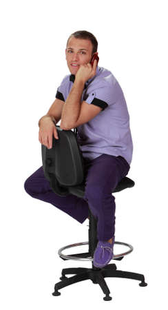 isolated chair: Young man on the phone while sitting on a chair, isolated against a white background