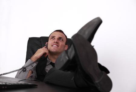 answering phone: Relajado joven empresario respondiendo a la llamada de tel�fono en la oficina con las piernas sobre el escritorio, sobre un fondo blanco Foto de archivo