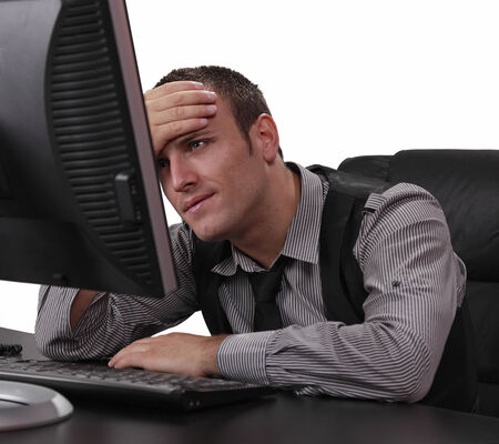 businessman in office: Unhappy young businessman in front of his computer at the office