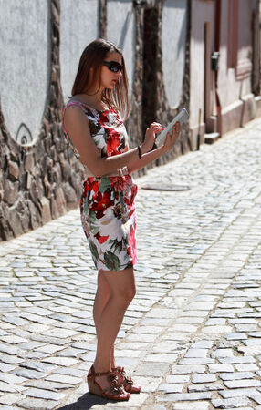 Young woman in the city using a map on a tablet for orientation. photo