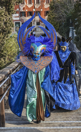 academia: Venice,Italy-February 18, 2012  Two unidentified persons disguised in blue costumes walking on the Academia Bridge in Venice during the Venice Carnival days