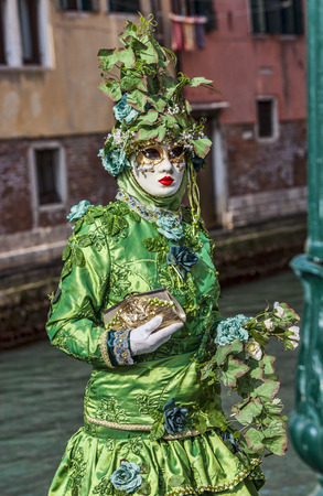 sestiere: Venice, Italy- February 18th, 2012 Environmental portrait of a person in sophisticated green Venetian costume posing in Sestiere Castello during The Venice Carnival days  Editorial