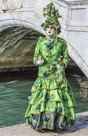 sestiere: Venice, Italy- February 18th, 2012 Image of a person in sophisticated green Venetian costume posing in Sestiere Castello during The Venice Carnival days