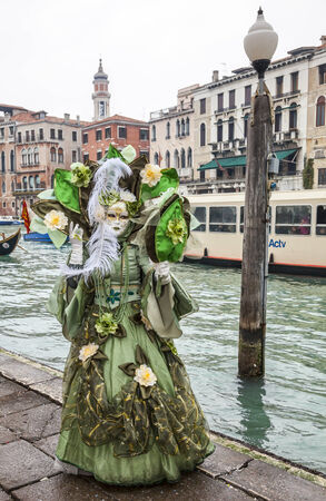 waterbus: Venice, Italy-February 19, 2012  Image of a person disguised in a complex green costume near the Grand Canal during the Venice carnival days