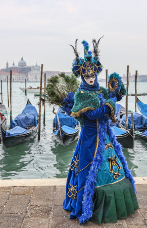 Venice, Italy- February 19, 2012  A person disguised in a beautiful blue disguise holding a mirror pose in San Marco Square in front of the gondola