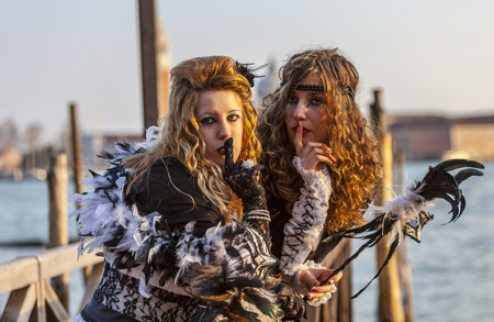 Venice, Italy-February 18,2012  Portrait of two young women with a secretive attitude posing near the gondola