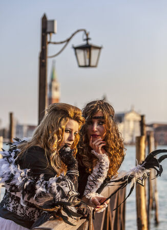 Venice, Italy-February 18,2012  Portrait of two young women wearing a beautiful specific costume near the gondola