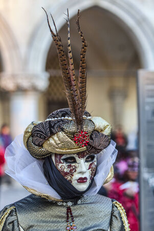 Venice, Italy- February 18th, 2012  Portrait of a person in a Venetian mask with pheasant feathers in San Marco Square during the Venice Carnival days