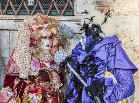 Venice, Italy- February 18th, 2012  Image of two persons disguised in specific costumes posing near the Doge