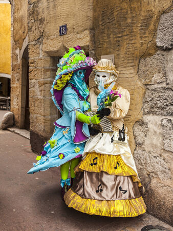 Annecy,France-March 15,2014 Two disguised persons looking in a fancy mirror on a narrow street between traditional houses, during the Annecy Venetian Carnival  Yearly in Annecy ,France is held a Venetian Carnival to celebrate the beauty of the real Venice
