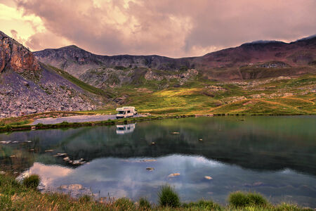 Colorful sunset over the Lake Essaupres located at 2306 m altitude near one of the highest asphalted road in Europe which lead to Col de la Bonette  2715 m  in Alpes-de-Haute-Provence, south of France  photo
