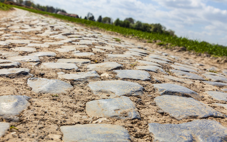 Low angle and tilted perspective of a cobbelstone road located in the North of France near Lille  On such roads every year is organized one of the most famous one day cycling race Paris-Roubaix  Stock Photo