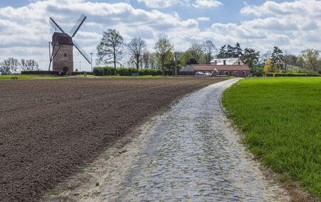 course cycliste: route Cobbelstone situ� dans le Nord de la France pr�s de Lille, � proximit� d'un moulin � vent traditionnel Moulin de Vertain Sur ces routes chaque ann�e est organis� l'un des plus c�l�bre v�lo d'une journ�e course Paris-Roubaix