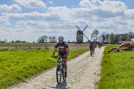 amateur: Templeuve, 5 Francia-abril de 2014: Un grupo de ciclistas aficionados montando sus bicicletas en la carretera de adoquines cerca del Moulin du Verlain en el norte de Francia, pocos días antes del paso del pelotón durante una de la más famosa carrera ciclista de un día: Paris -R Editorial