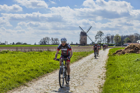 pave: Templeuve,France- April 5, 2014:A group of  amateur cyclists riding their bicycles on the cobblestone road near the Moulin du Verlain in Northern France,few days before the passing of the peloton during one of the most famous one day cycling race: Paris-R Editorial