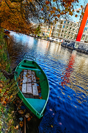 green boat: A green boat on a canal in Amsterdam during the autumn