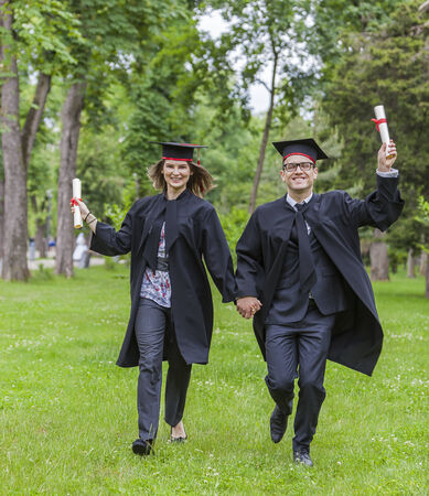 Young happy couple running in a green park in the graduation day  photo