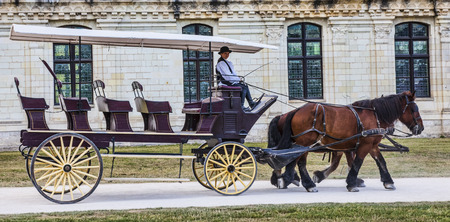Chambord,France-September 08,2013  A carriage with a female coachman passing in front of the Chambord Castle  Chambord is royal medieval French castle in Loire Valley - UNESCO heritage site