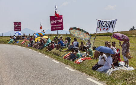 Col de Manse, France- July 16, 2013 Group os spectators waiting for the peloton on a plain road after the ascension to Col de Manse in The Alps during the stage 16 of 100th edition of Le Tour de France 2013 They made a special basket for collecting the fl