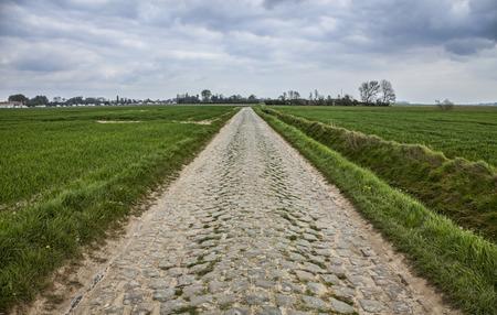 course cycliste: route Cobbelstone situ� dans le Nord de la France pr�s de Lille. Sur ces routes chaque ann�e est organis� l'un des plus c�l�bre v�lo d'une journ�e course Paris-Roubaix. Banque d'images