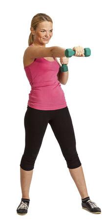 Mujer rubia joven que hace ejercicio con pesas aislados sobre un fondo blanco.